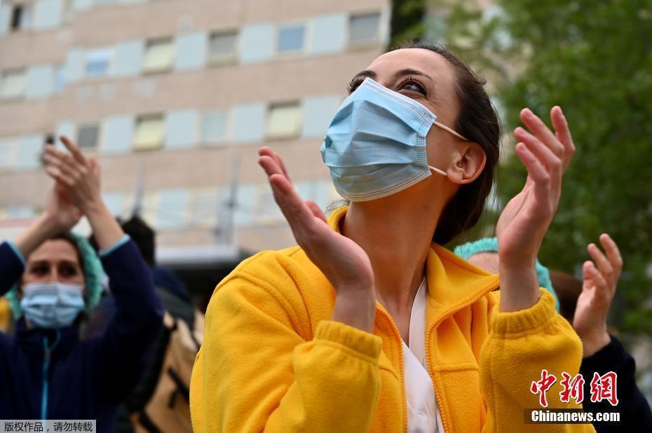 西班牙医护人员为禁闭在家的民众鼓掌加油